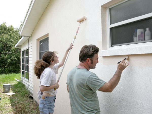 Father and daughter painting stucco walls one of the popular exterior home colors in Vista