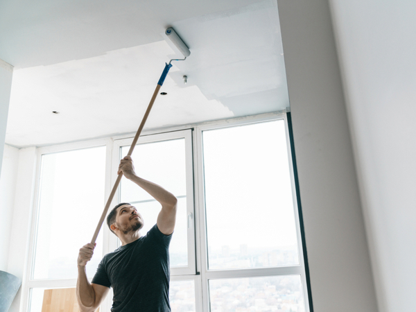 Man painting a ceiling with a roller on a pole