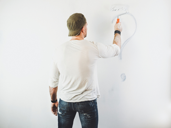 Man painting over a question mark on a wall