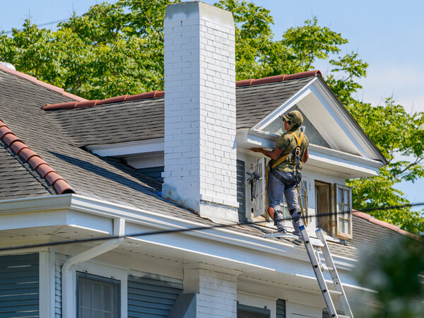 Man painting exterior trim on top of home
